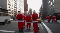 A group of young men dressed as Santa Claus cross a busy intersection Stock Footage