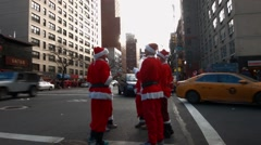 Four young men dressed as Santa Claus congregate together in dangerous traffic Stock Footage
