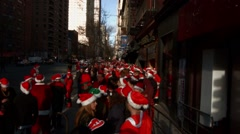 Hundreds of young men and women dressed as Santa Claus wait together Stock Footage