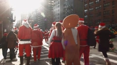Many young men and women dressed as Santa Claus cross a busy street intersection Stock Footage