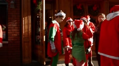 Multiple Young men and women dressed as Santa Claus exit a restaurant Stock Footage