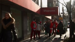 Young men and women dressed as Santa Claus walk past a drug store Stock Footage