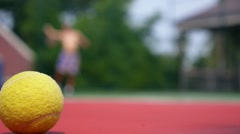 Tennis Ball in Focus on Court with the Net and Player Stock Footage