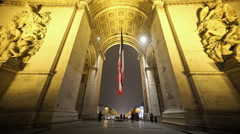 Wide angle shot of Arc de triomphe with French Flag by night Stock Footage