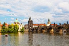 Prague, view of karlov bridge and tourists going on it Stock Photos