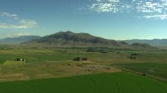 Aerial USA Idaho farming crops vegetation mountain farmland plain Stock Footage