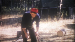 1400 man is chopping firewood for camp - vintage film home movie Stock Footage
