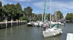 Sailing boat leaving the small Maartensgat harbour in Dordrecht, Netherlands. Stock Footage