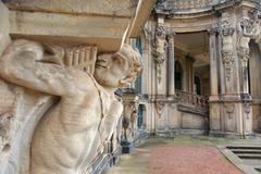 closeup half naked faunus statue under column with panpipe at zwinger palace  - stock photo