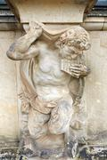 closeup half naked satyr statue playing panpipe at zwinger palace - stock photo