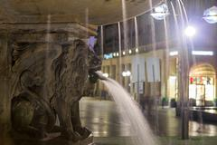 lion statue with streaming water from mouth near cologne cathedral - stock photo