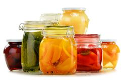 Stock Photo of jars with pickled vegetables and fruity compotes isolated on white background