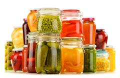 Stock Photo of jars with pickled vegetables, fruity compotes and jams isolated on white back