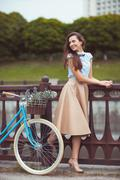 young beautiful, elegantly dressed woman with bicycle - stock photo