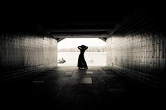 Silhouette of a girl on bright background in a tunnel Stock Photos