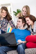 Group of teenagers watching looks funny clip online Stock Photos