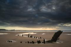 Stock Photo of landscape image of old shipwreck on beach at sunset in summer