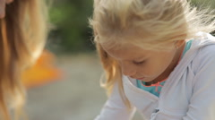 Beautiful little girl with pierced ears eats delicious cakes with fruits Stock Footage