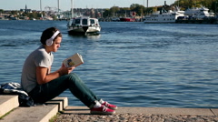 Reading a book by the sea and listening to a music in a sunny day Stock Footage