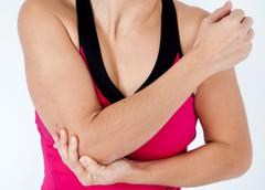 Young woman having pain in his elbow - sports injury Stock Photos