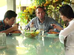 Happy family talking and eating spaghetti at home NTSC Stock Footage