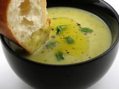 Chunk of bread dipped into cream soup Stock Photos
