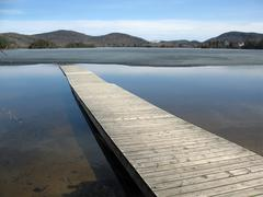 dock juts into half-frozen lake - stock photo