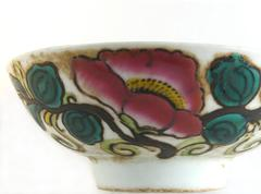 Antique ceramic chinese bowl with pink flowers and green leaves. Stock Photos