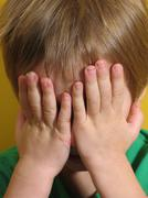 Small child covers face with  hands as though counting for hide-and-seek. Stock Photos