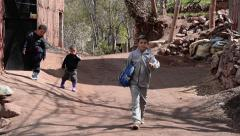 Children in the age of three and four on a road in small country village - stock footage