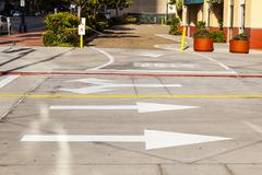 arrows and lines on the asphalt to indicate the direction of driving - stock photo