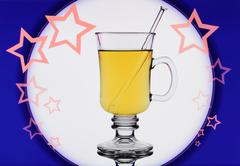 yellow mulled wine on blue background with stars - stock photo
