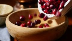 Cranberries pouring into wooden bowl, slow motion Stock Footage