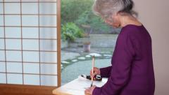 "Senior Asian Woman Writing Kanji Character for ""Heart"" Stock Footage"