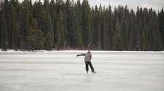 Man ice skating on frozen lake with forest in background Stock Footage