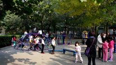 Children play freely at the Ditan Park in Beijing, China Stock Footage