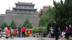 Local people singing Qinqiang opera under the ancient city gate Stock Footage