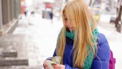 Girl count money on street to buy something she likes Stock Footage
