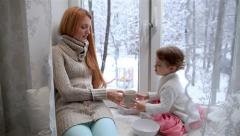 Young mother and her daughter sitting on the windowsill drinking tea. Dolly shot Stock Footage