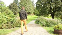 Man walking calm on beautiful garden on holidays, new beginning - stock footage