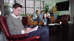 Portrait of cheerful young man writing on a notepad in shared apartment - stock footage