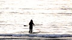 Paddle surfer at sunset in Enoshima, Kanagawa Prefecture, Japan Stock Footage