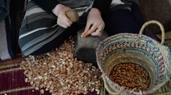 Hands of a woman who is breaking argan nuts Stock Footage