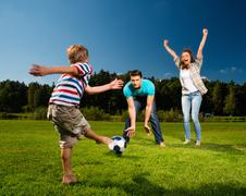 Happy young family playing football outdoors Stock Photos