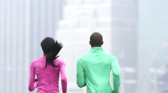 A couple runs away from the camera in slow motion with the city behind them Stock Footage