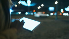 Woman using touch pad while walking in city at night Stock Footage