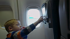 Little boy touching seat monitor in plane Stock Footage