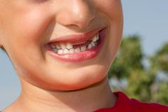 Child plays a cheerful smile without showing teeth Stock Photos