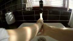 POV clip of a woman washing her hands in a kitchen sink - stock footage