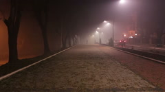 A man walking down the street through the fog. Cars in fog. Street lights. Stock Footage